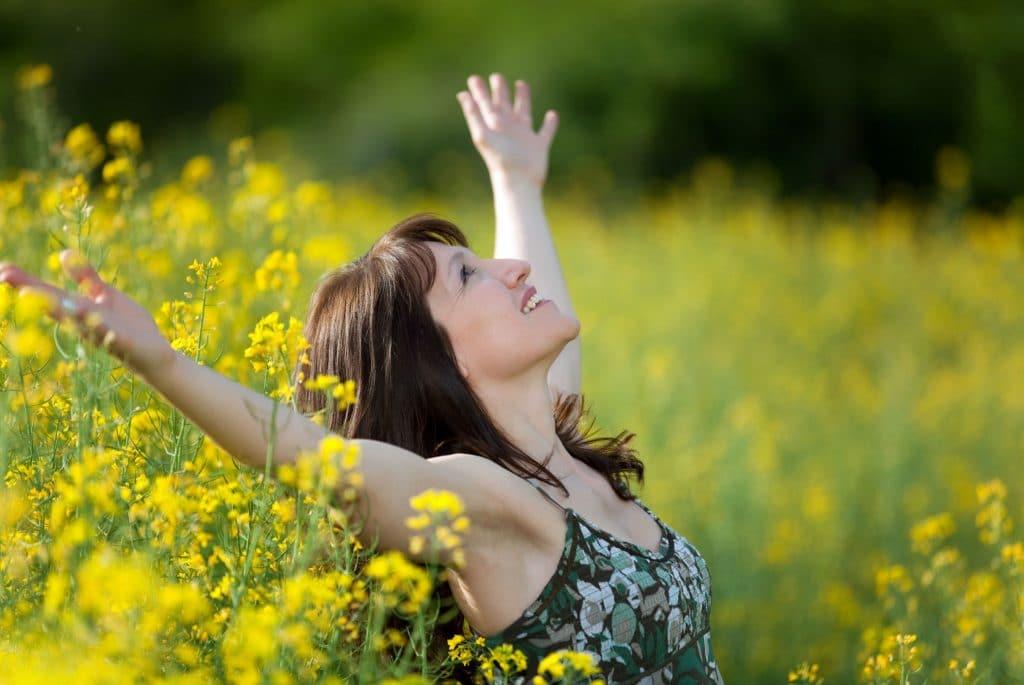 Happy woman in field of yellow flowers